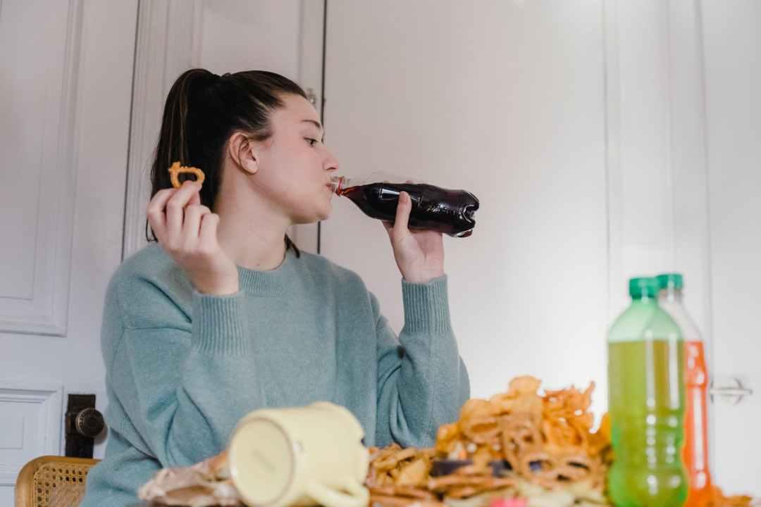 woman drinking fresh lemonade at table with junk food