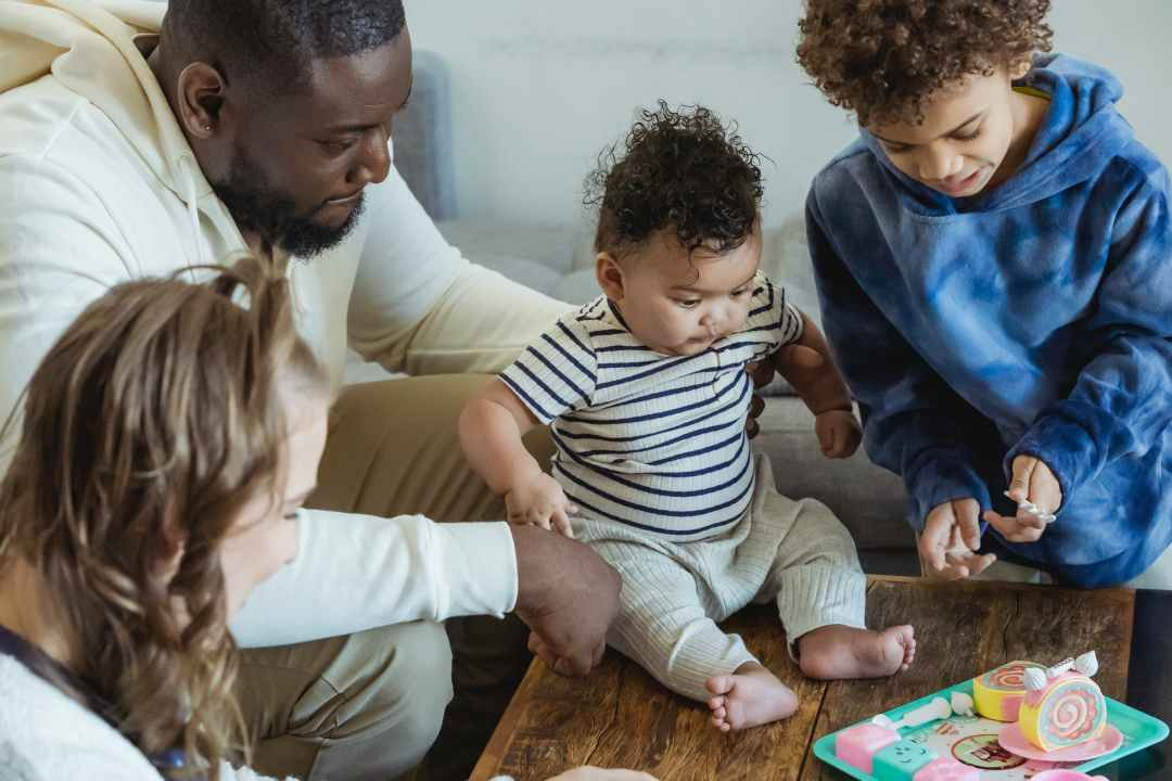 crop smiling diverse family playing in house room