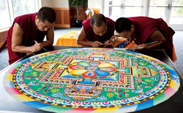 monjes tibitanos creando un mandala con arena