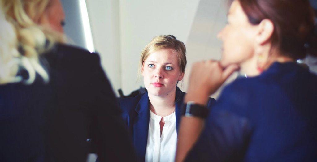 Imagem mostra uma profissional de psicologia debatendo um estudo de caso com duas outras profissionais de outras áreas, talvez psicanálise e medicina. Todos os profissionais trabalhando em conjunto no mesmo caso, porém de formas próprias à suas profissões.
