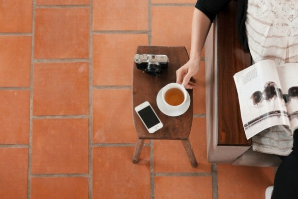 Pessoa lendo e bebendo café.