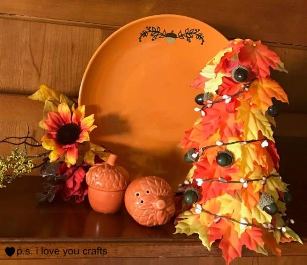 Make an easy fall table decoration using a styrofoam cone, silk leaves, straight pins, acorns, and a small fall garland.