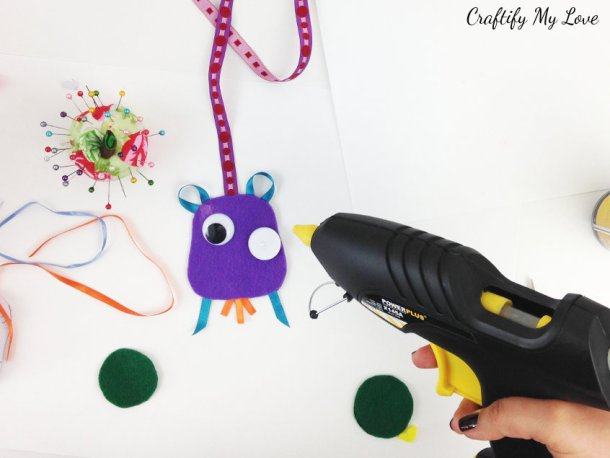 attaching wiggly eyes with hot glue to felt craft owl bookmark