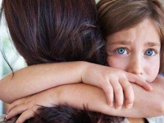 Niña abraza a su madre con teoría del apego