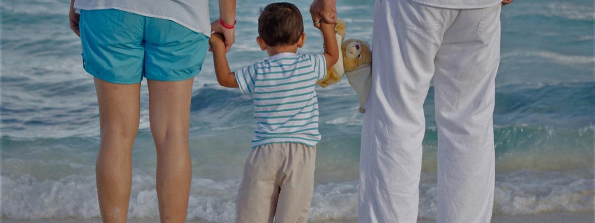 Foto de niño entre sus padres mirando el mar.