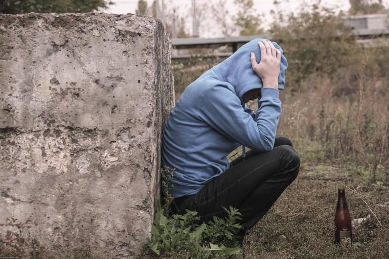 Foto de adolescente en el campo con capucha en la cabeza y manos en la cabeza.