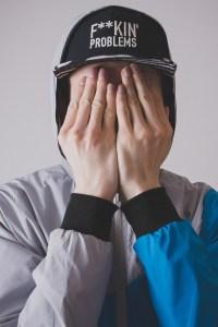 Foto de hombre con gorra que se cubre la cara con ambas manos.