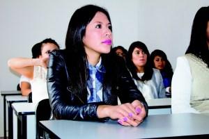 Estudiante con labios y uñas azules mirando atenta al profesor en clase