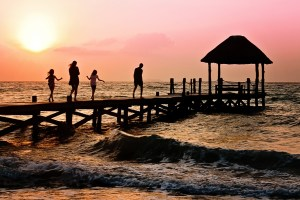 Foto de una familia andando sobre un puente en el mar.