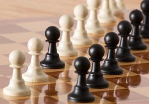 Fotografía de piezas blancas y negras de una ajedrez enfrentadas recíprocamente