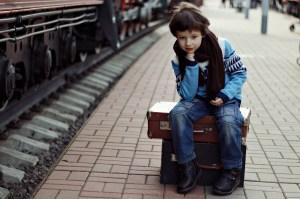 Fotografía de un niño sentado en una maleta a lado de la via del tren