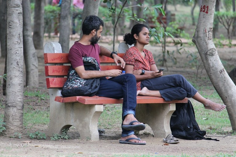 Imagen de una pareja sentada en un banco sin hablarse