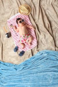 fotografía de un bebé tumbado en una toalla de mar con las gafas de sol