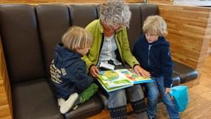 Fotografía de una persona mayor compartiendo un libro con dos niños