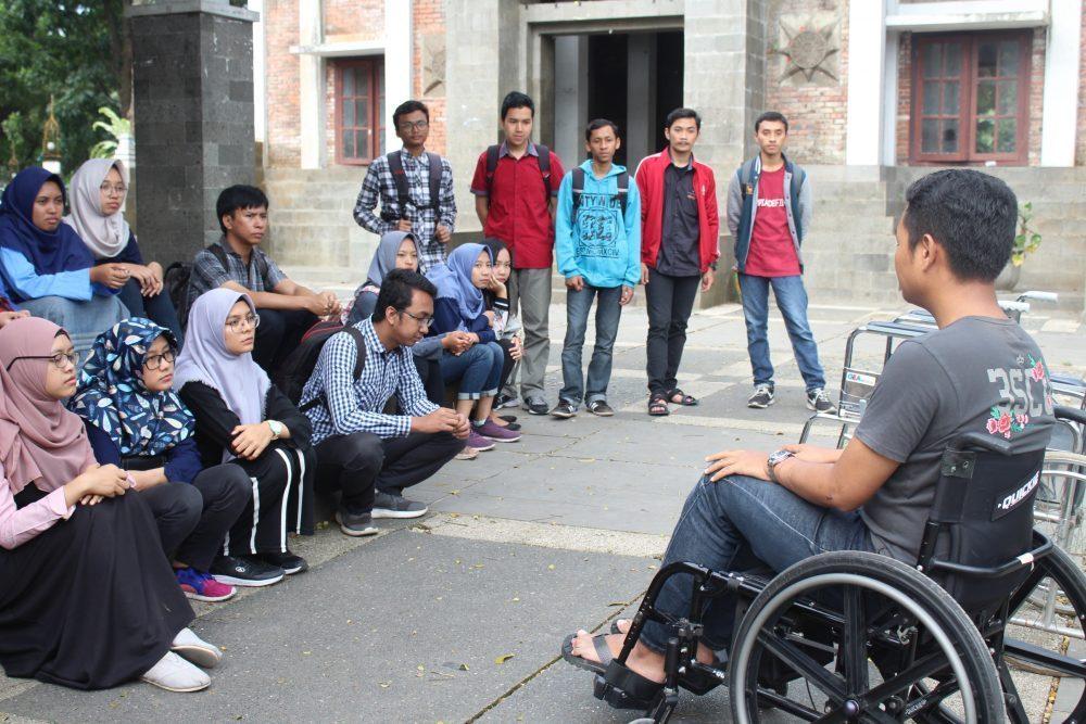 Ghani, salah satu fasilitator disability awareness untuk panitia Raja Brawijaya, menjelaskan fasilitasi penyandang disabilitas pengguna kursi roda di depan panitia Raja Brawijaya 2018. Pelatihan ini berlangsung di Gazebo UB pada 29 Juli 2018.
