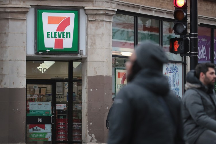 Pedestrians walk past a 7-Eleven store on January 10th, 2018, in Chicago, Illinois.