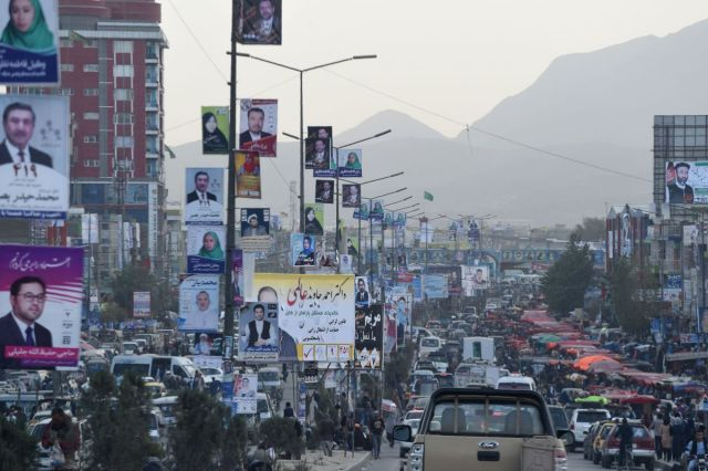 Kabul commuters drive along a road with posters of candidates hanging from street posts.
