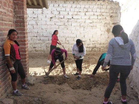 The girls breaking up the earth in the new site.