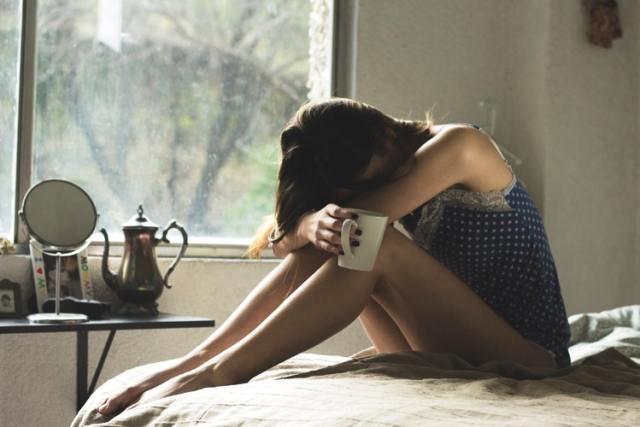 Woman bending over on a bed, her head between her knees as if crying. She is holding a while mug and there is a window behind her with greenery.