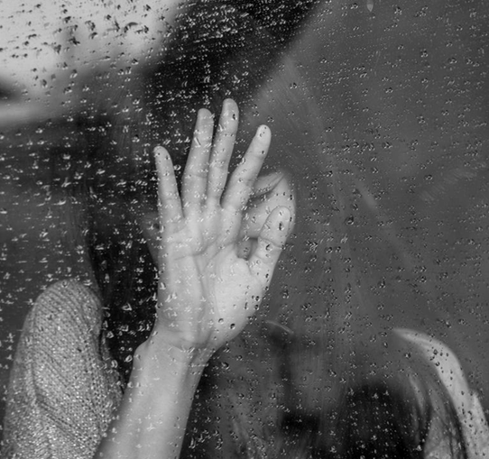 black and white picture of woman leaning her hand against a rainy window banner childhood abuse