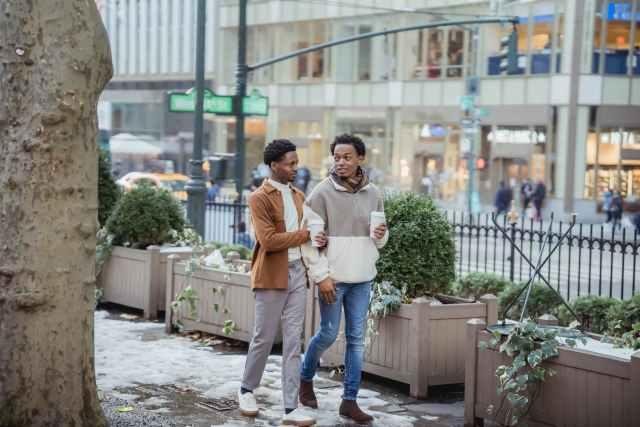 cheerful black homosexual couple with coffee walking on snowy sidewalk