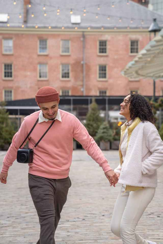 cheerful hispanic couple smiling and holding hands on urban street