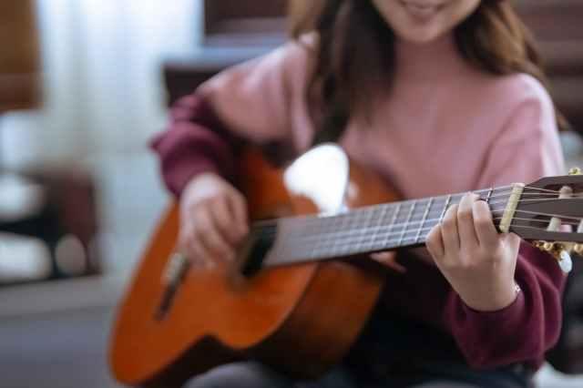 crop woman playing guitar near piano