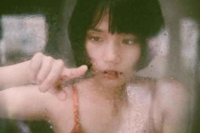 ethnic female touching wet window