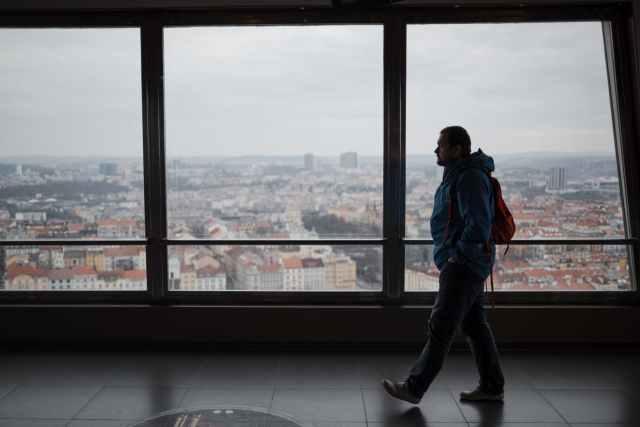 man walking along windows in modern building