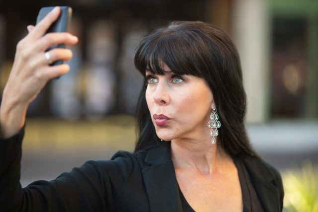 44954005 - attractive woman taking selfie with black cell phone