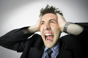 business portrait of a young adult male in a suit as he holds his head and screams