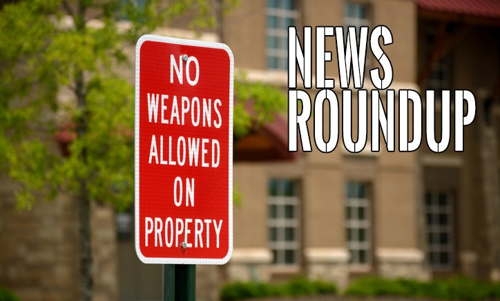 A bright red sign in front of a public school stating there are no weapons allowed.