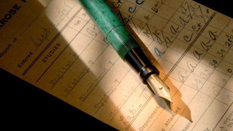 Vintage Fountain Pen and 1928 Report Card Under Dramatic Light