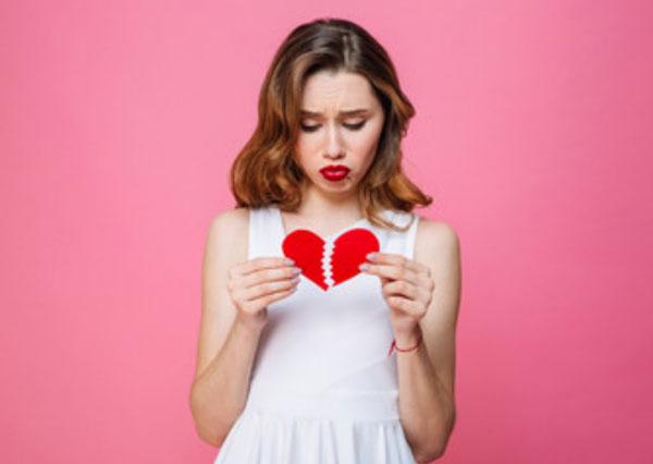 Девушка разрывает бумажное сердце