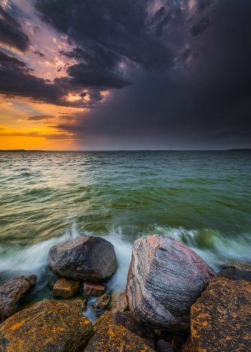 brown rocks on sea under cloudy sky during sunset