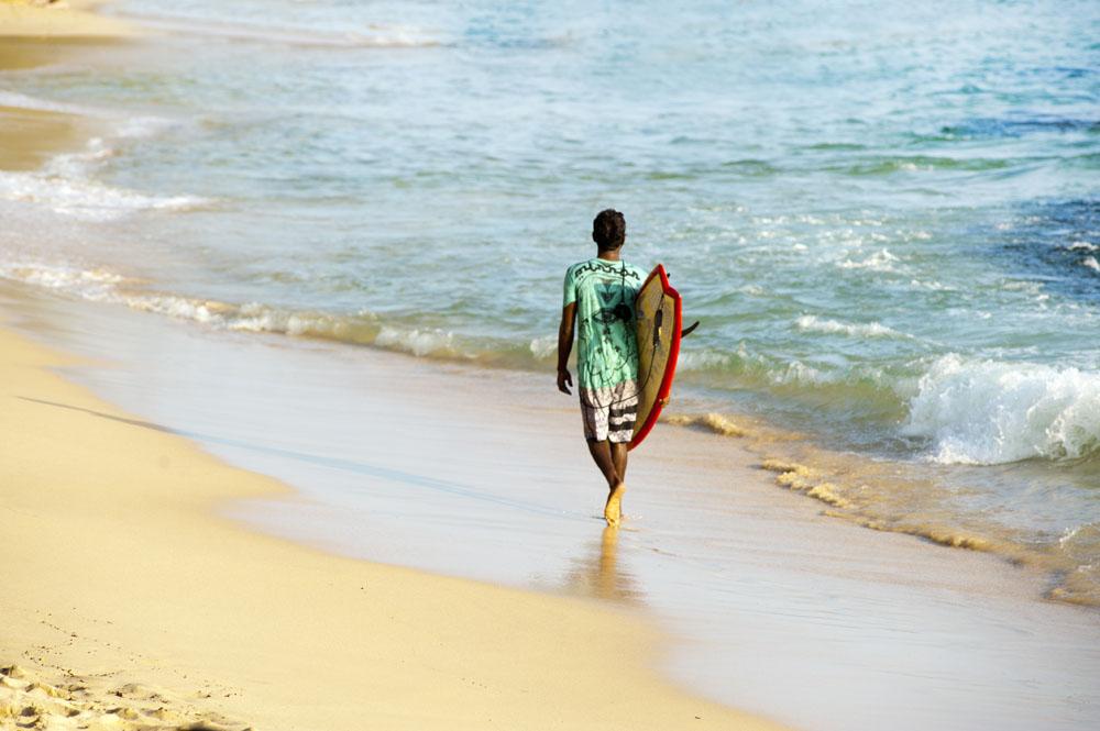 Chico en la playa con tabla de surf