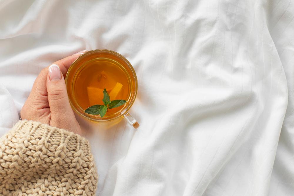 mano sosteniendo taza té con menta