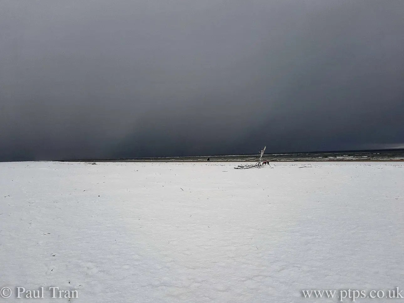 storm clouds over a snow-covered beach