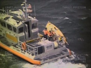 A Coast Guard 45-foot Response Boat-Medium crew from Station Port Angeles, Wash., rescues a man after his sailboat overturned near Port Townsend - (U.S. Coast Guard picture by Petty Officer 3rd Class Sean Farrar)