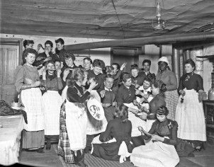 Large group of women of varying ages wearing aprons and sitting together, possibly at a candy pull, ca. 1904