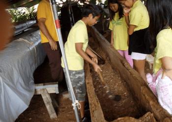 ala wai elementary students carving a koa canoe