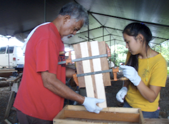 uncle bobby helping punahou student maya make a paddle