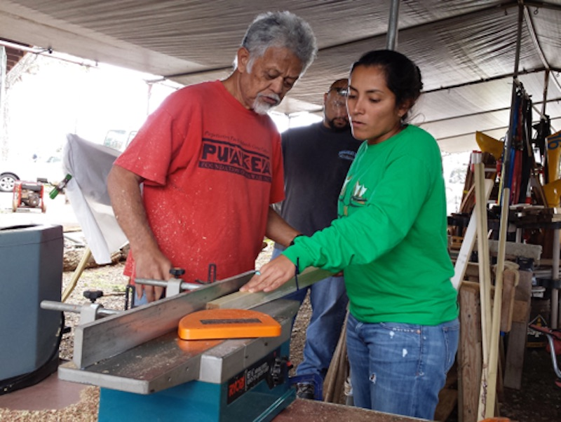 Photo of Uncle Bobby Puakea teaching a student in his paddle workshop