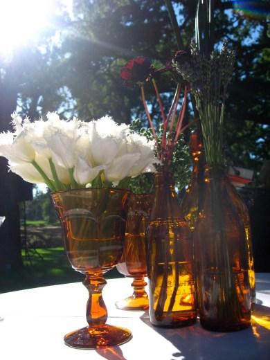 Gorgeous cocktail table arrangements in vintage bottles.