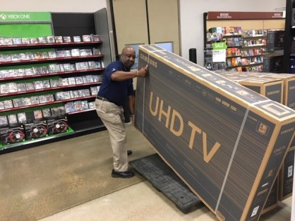 Tyrone Jones, retail management trainee, lifts a large UHD TV at the Barksdale Exchange.