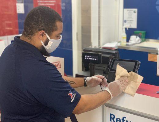 Wiesbaden Exchange Customer Experience Associate Eric Richardson sanitizing a PIN pad
