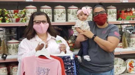 Exchange shopper Martha Alaniz and granddaughter Jolina Tynes pick up winter clothes for Alaniz's three grandchildren Oct. 14 at the Fort Hood Exchange. Alaniz was one of 52 lucky shoppers notified this week that their Exchange layaway balances were paid in full by the nonprofit Pay Away the Layaway. Also pictured, Fort Hood Main Store Manager Teresa Palu.