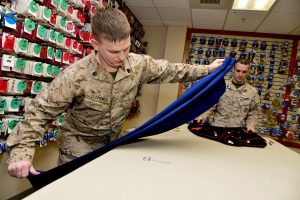 Staff Sgt. John Clements, left, and Corp. Landon Beaty, Air Force Mortuary Affairs Operations, assemble a dress blues uniform for a fallen Marine. (U.S. Air Force photo/David Tucker)