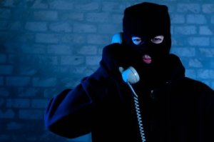 A person in all black, with a black ski mask, talking on a corded phone.