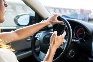 A young woman with long hair texting while driving.